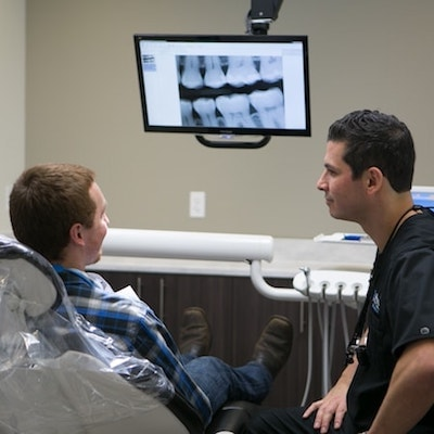Dr. Youssef talking to a patient who is going through a dental emergency. Call us at 206-489-2926 if you're going through a dental emergency