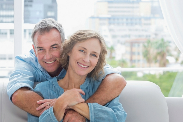 An older couple wearing blur shirts and embracing as they enjoy the benefits of dental implants in Edmonds WA